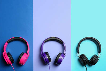 Stylish headphones on color background, flat lay. Space for text