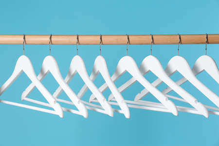 Wooden rack with clothes hangers on color background