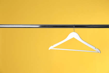 Metal rack with clothes hanger on color background, space for text