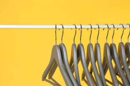 Metal rack with clothes hangers on color background, closeup. Space for text 版權商用圖片