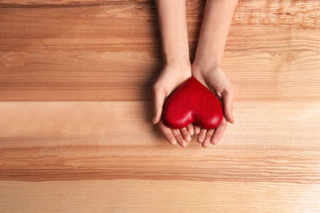 Woman holding decorative heart on wooden background, top view. Space for text