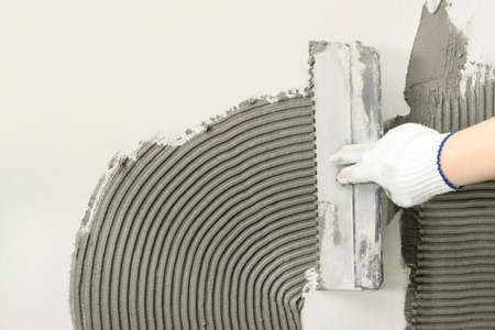 Closeup of worker spreading concrete on wall with spatula, space for text. Tile installation 写真素材