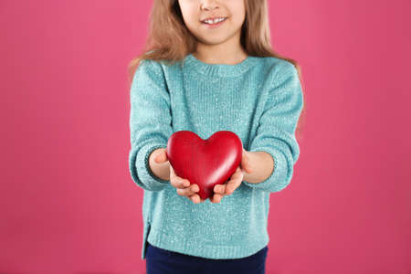 Girl with decorative heart on color background, closeup