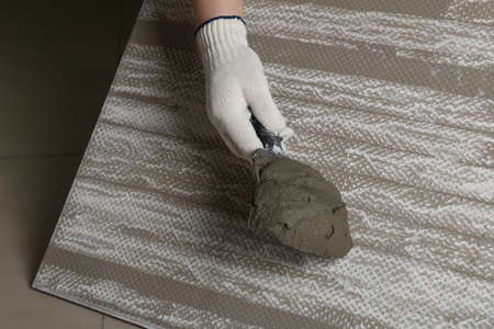 Worker holding adhesive mix on spatula above tile, closeup