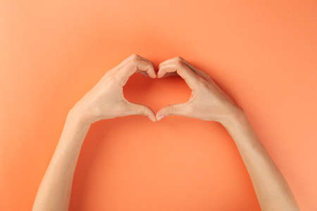 Woman making heart with her hands on color background, top view