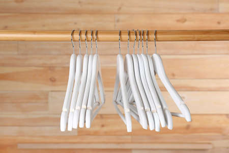 Rack with clothes hangers on wooden background 版權商用圖片