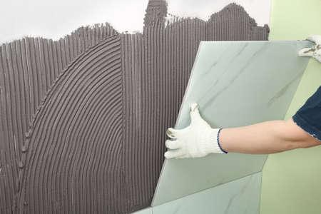 Arbeiter installieren Keramikfliesen an der Wand, Nahaufnahme. Platz für Text Standard-Bild