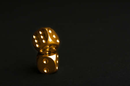 Stacked gold dices on black background. Space for text