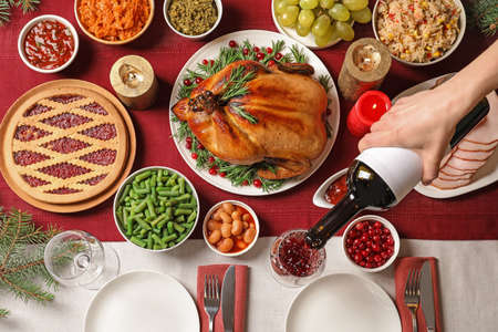 Woman pouring wine into glass at table with delicious roasted turkey for festive dinner, top view Stock Photo