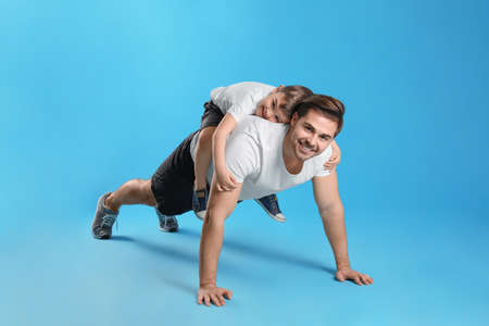 Dad doing push-ups with son on his back against color background
