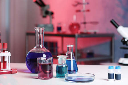 Different glassware with samples on table in chemistry laboratory Banco de Imagens
