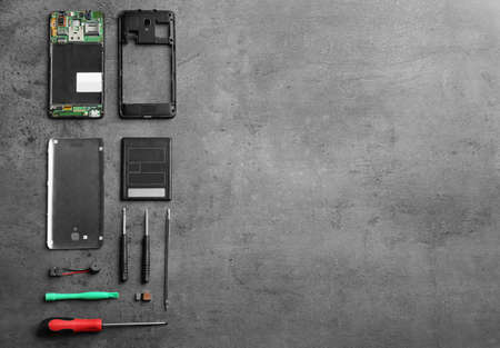 Disassembled mobile phone and repair tools on table, flat lay. Space for text