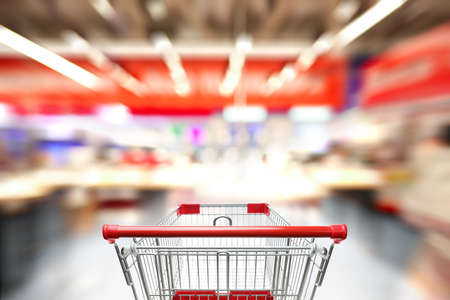 Blurred view of supermarket and empty shopping basket