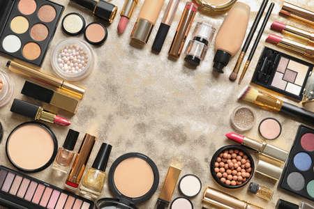Cadre composé de différents produits de maquillage de luxe sur fond doré, pose à plat. Espace pour le texte