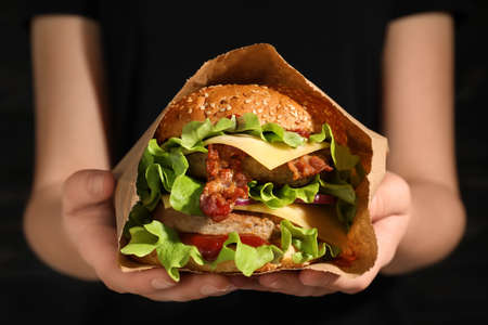 Donna che tiene gustoso hamburger con pancetta in un sacchetto di carta, primo piano