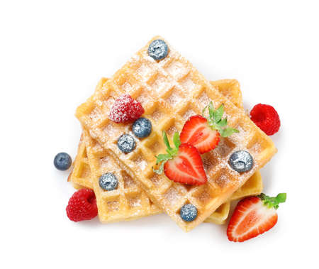 Delicious waffles with berries on white background, top view