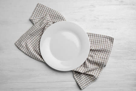 Empty plate and napkin on white wooden background, flat lay