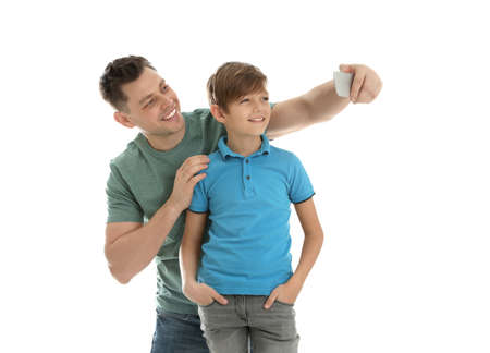 Dad and his son taking selfie on white background Фото со стока