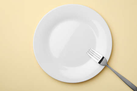 Empty plate and fork on color background, flat lay