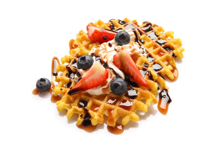 Delicious waffles with berries and whipped cream on white background