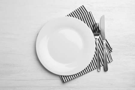 Empty plate, cutlery and napkin on white wooden background, flat lay