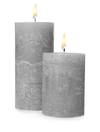 Two alight wax candles on white background