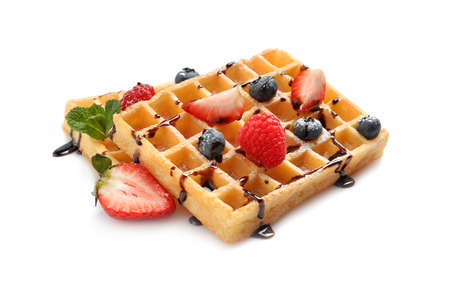 Yummy waffles with berries and chocolate syrup on white background Imagens