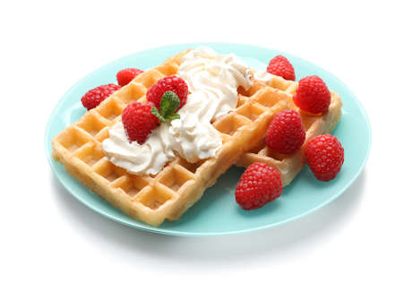 Plate with yummy waffles, whipped cream and raspberries on white background Imagens