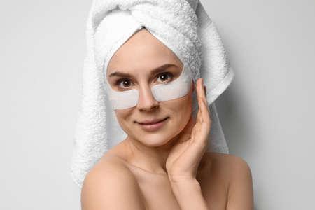 Piękna kobieta z przepaskami na oko na jasnym tle. Maska na twarz