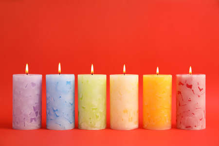 Alight scented wax candles on color background