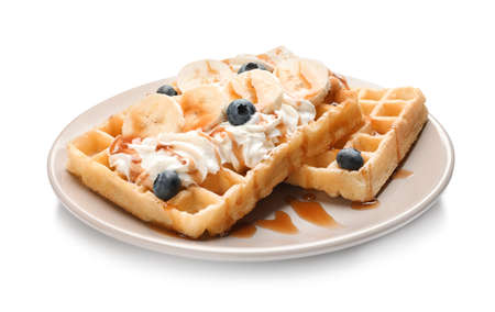 Plate with yummy waffles, whipped cream, blueberries and banana on white background