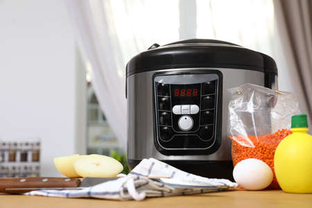 New modern multi cooker and products on table in kitchen. Space for text