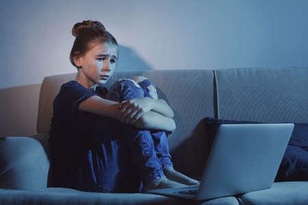 Frightened teenage girl with laptop on sofa in dark room. Danger of internet