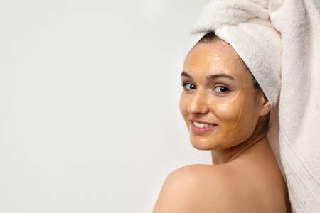 Mooie vrouw met masker op gezicht tegen lichte achtergrond. Ruimte voor tekst
