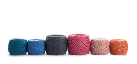 Clews of colorful knitting threads in row on white background