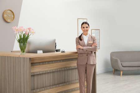 Portrait of receptionist near desk in modern hotel 免版税图像