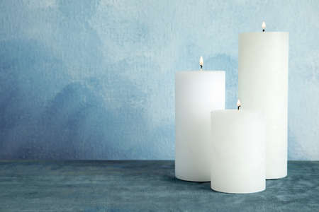 Alight wax candles on table. Space for text Stock Photo