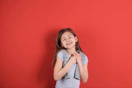 Portrait of girl holding hands near her heart on color background