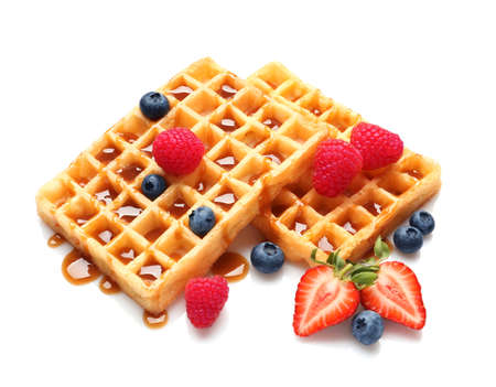 Yummy waffles with berries and caramel syrup on white background Imagens