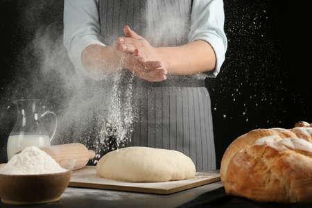 Baker femelle préparant la pâte à pain à la table de cuisine Banque d'images