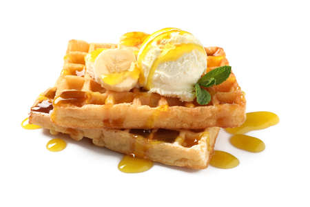 Delicious waffles with ice cream, banana and syrup on white background Imagens