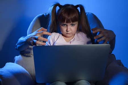 Stranger reaching little child with laptop on color background. Cyber danger