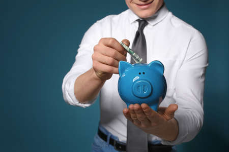 Businessman putting money into piggy bank on color background, closeup. Space for text