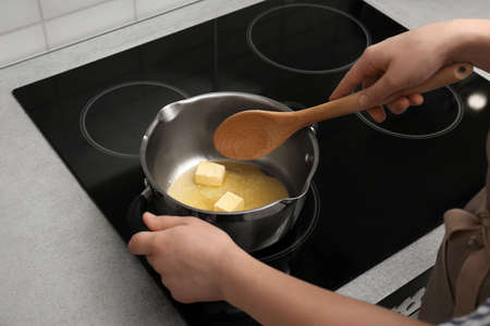 Femme en remuant le beurre dans une casserole sur une cuisinière électrique, gros plan