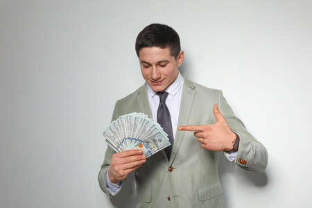 Portrait of young businessman with money fan on light background