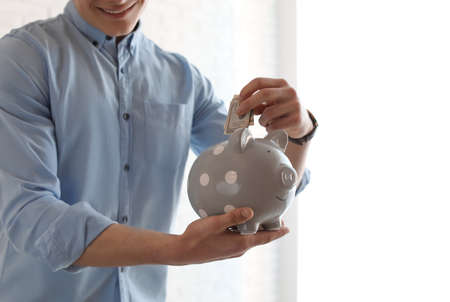 Young businessman putting money into piggy bank indoors, closeup. Space for text Stock Photo