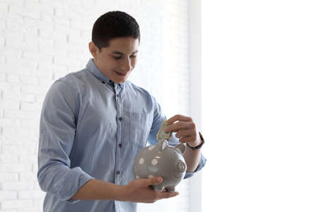 Young businessman putting money into piggy bank near brick wall. Space for text