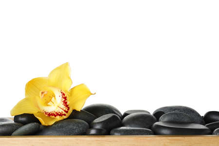 Wooden tray with spa stones and orchid flower against white background Stock Photo