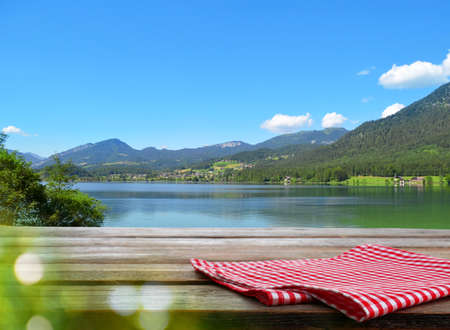 Empty wooden table with checkered napkin outdoors, space for design. Summer picnic 版權商用圖片