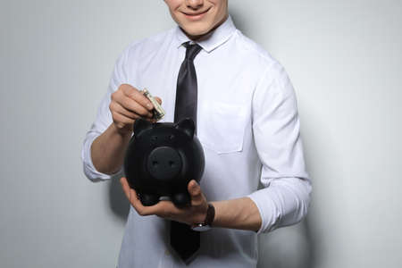 Young businessman putting money into piggy bank on light background, closeup